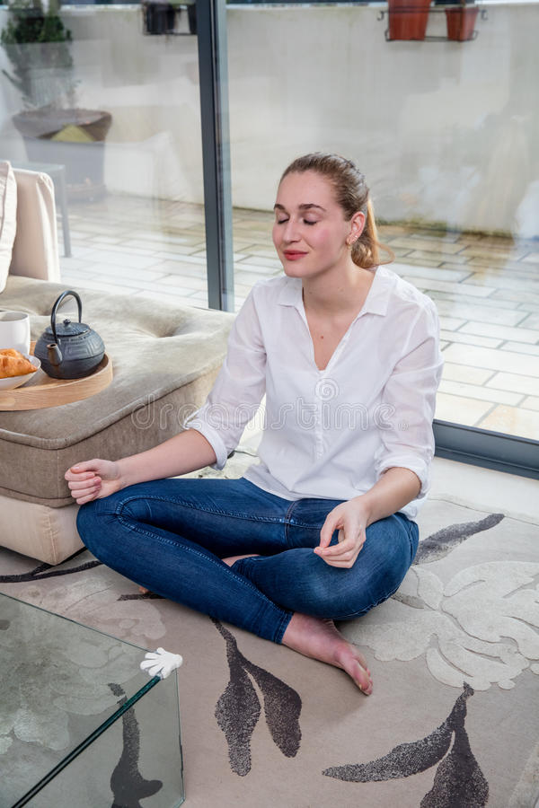 Smiling young woman relaxing sitting in lotus position on floor stock photos