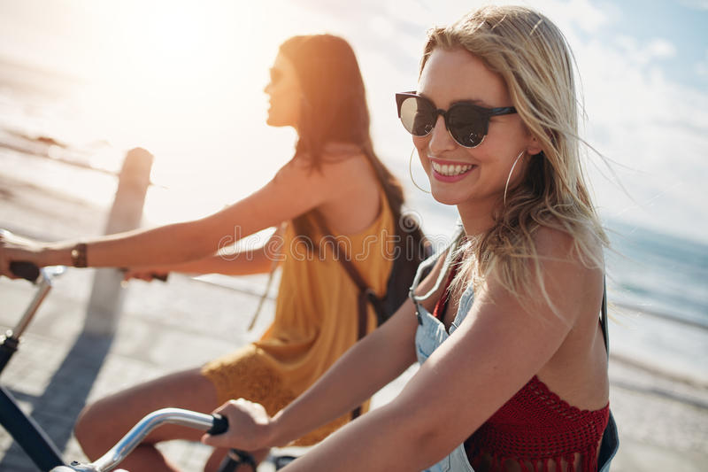 Smiling young woman riding bicycle with her friend royalty free stock image