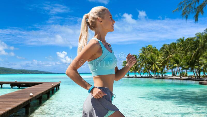 Smiling young woman running along exotic beach royalty free stock image