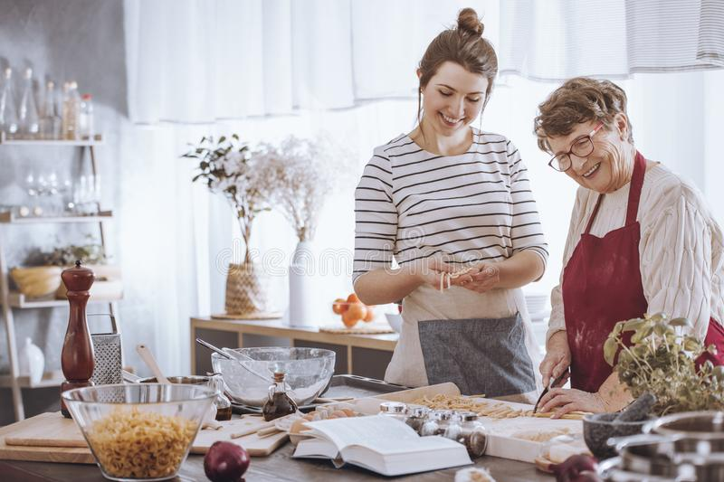Smiling young woman shaping dough royalty free stock photography