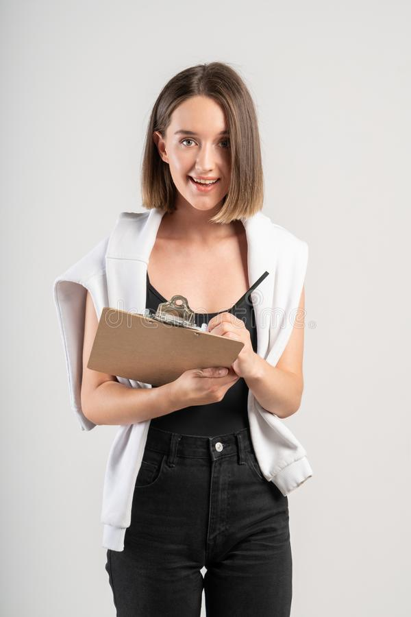 Smiling casual woman writing in clipboard royalty free stock photo