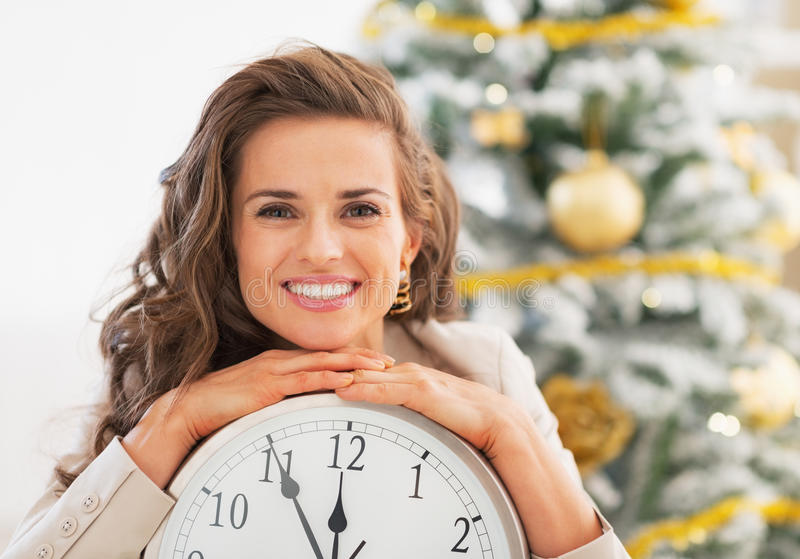 Smiling young woman showing clock in front of christmas tree. Portrait of smiling young woman showing clock in front of christmas tree in living room royalty free stock image