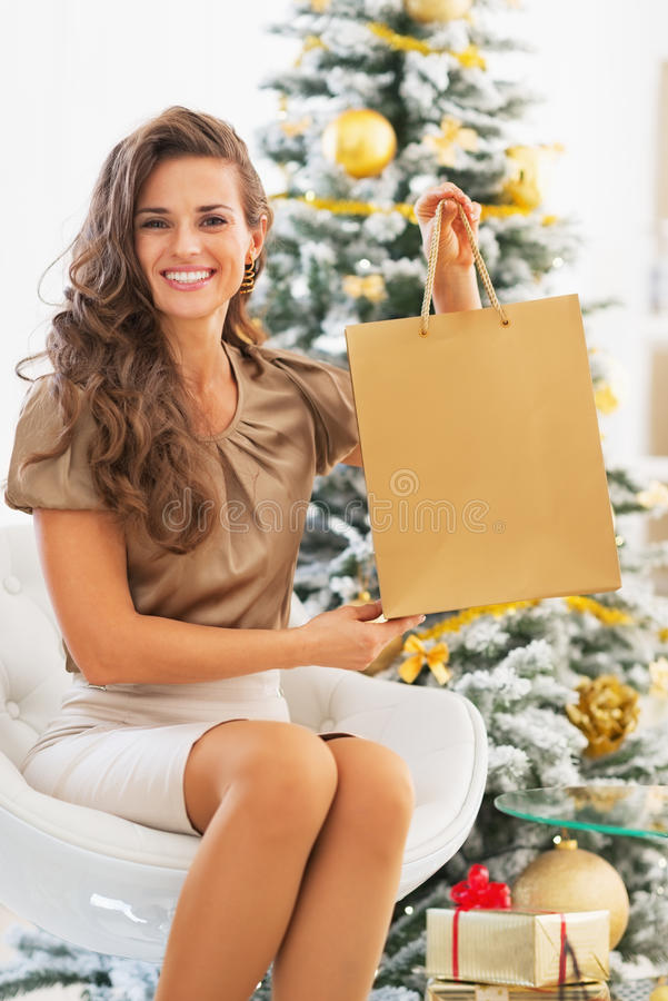 Smiling young woman showing shopping bag near christmas tree. In living room stock photo