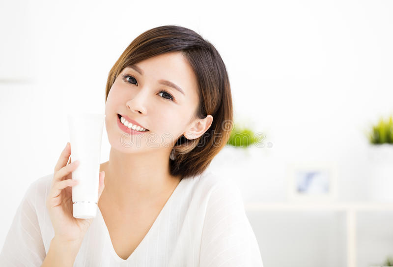 Smiling young woman showing skincare products. Smiling young asian woman showing skincare products stock photos