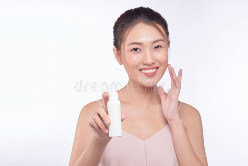 Smiling young woman showing skincare products.  stock photo