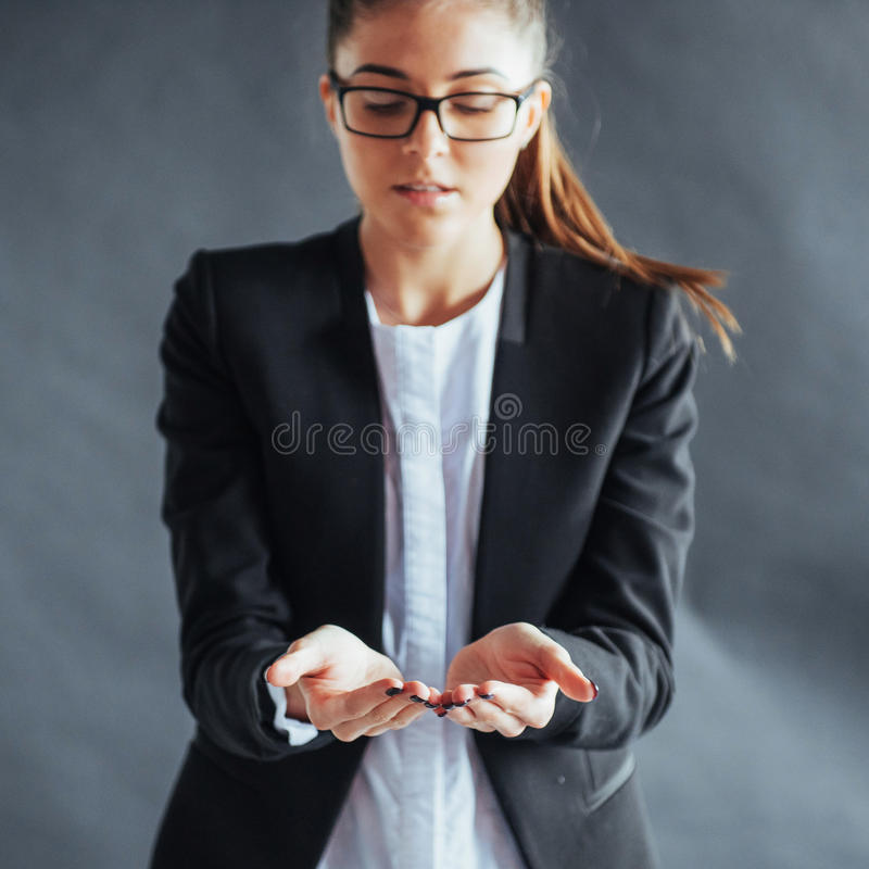 Smiling young woman showing something on the palm of both hands open stock photos