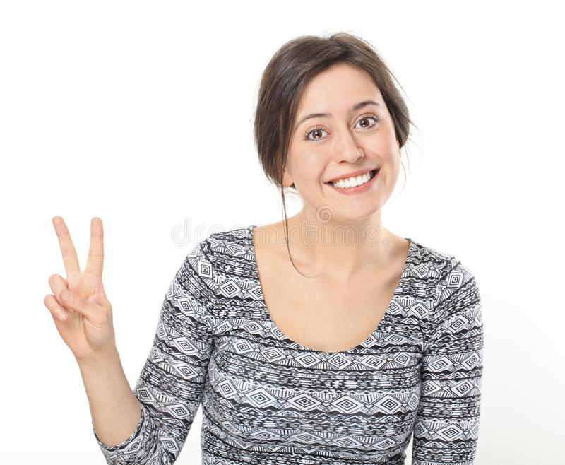 Smiling young woman showing victory or peace stock photo