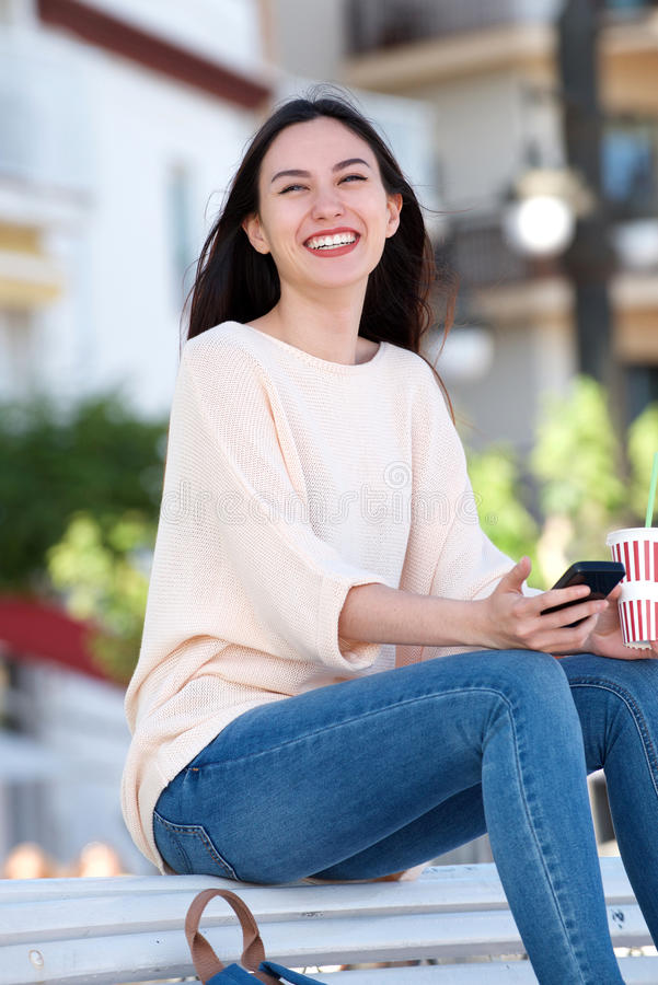 Smiling young woman sitting on bench with drink and phone royalty free stock image