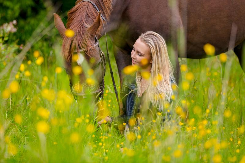 Smiling woman sits in the meadow with her beautiful arabian horse stock image