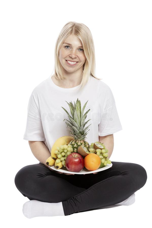 A smiling young woman is sitting with a plate of fruit in her hands. Isolated over white background. stock photos