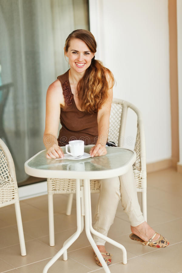 Smiling young woman sitting on terrace stock images