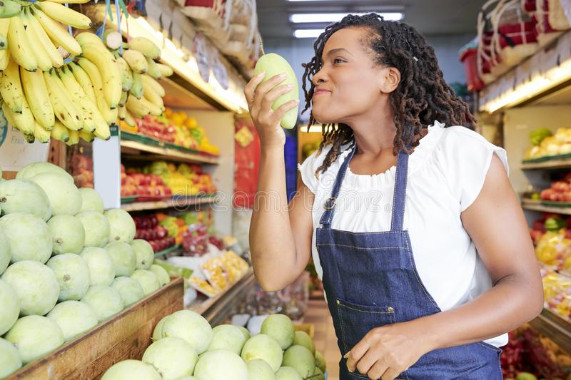 Woman smelling mango in store stock image