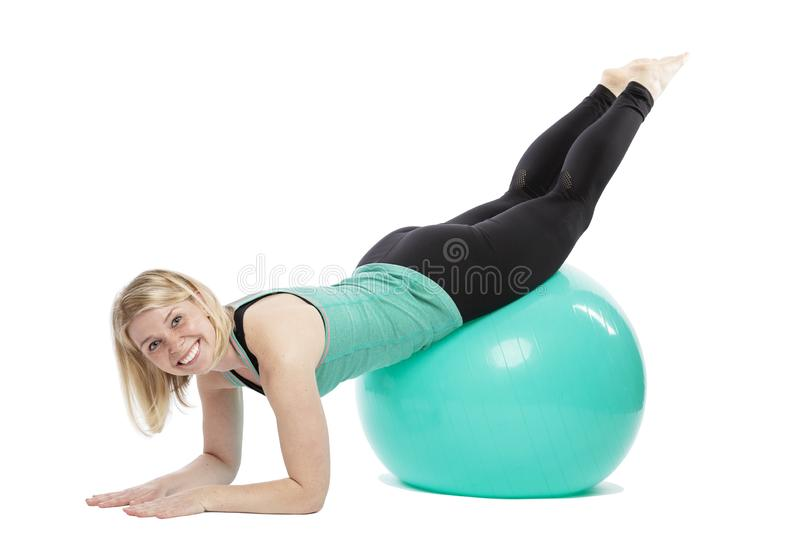 Smiling young woman in sportswear doing exercises with fitness ball. Isolated over white background royalty free stock image