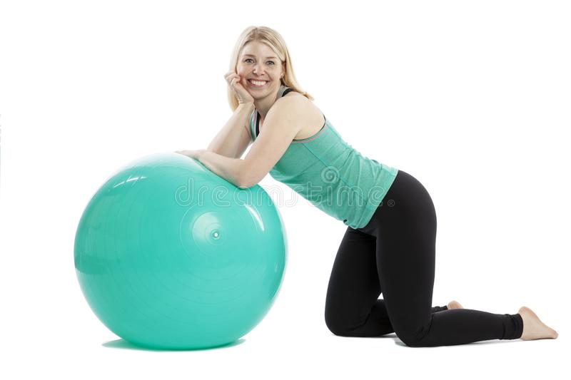 Smiling young woman in sportswear doing exercises with fitness ball. Isolated over white background royalty free stock photography
