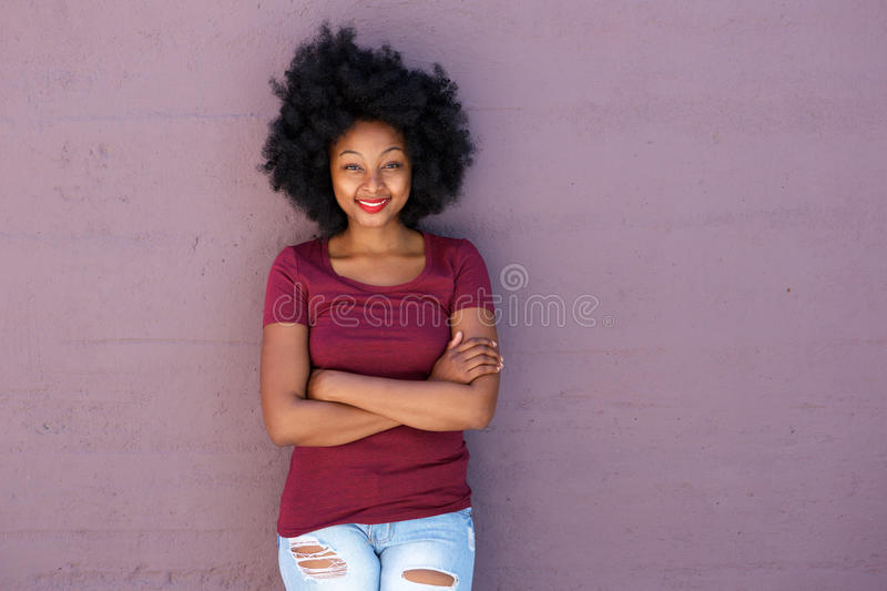 Smiling young woman standing by wall with arms crossed royalty free stock photos
