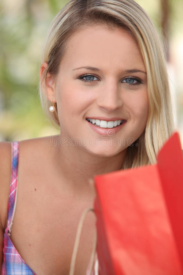 Smiling young woman with a store bag