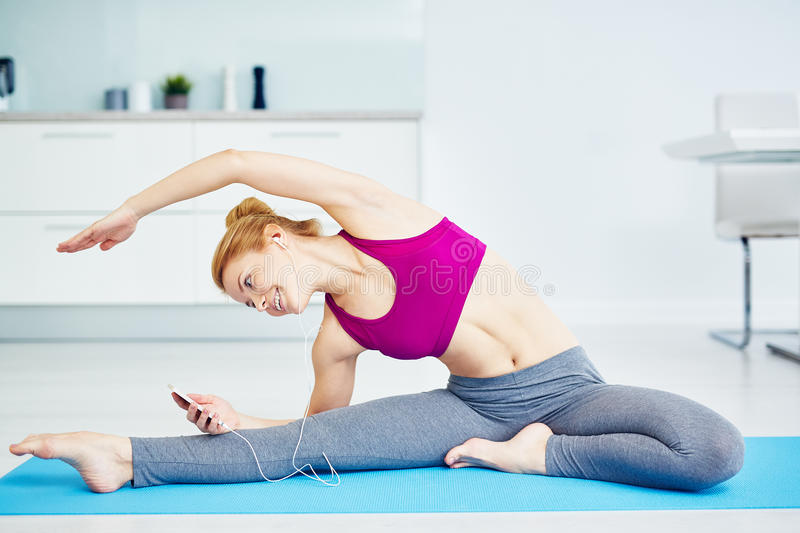 Smiling Young Woman Stretching with Smartphone stock photography