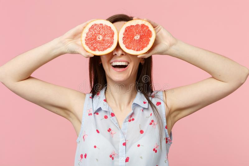 Smiling young woman in summer clothes covering eyes with halfs of fresh ripe grapefruit isolated on pink pastel stock photo