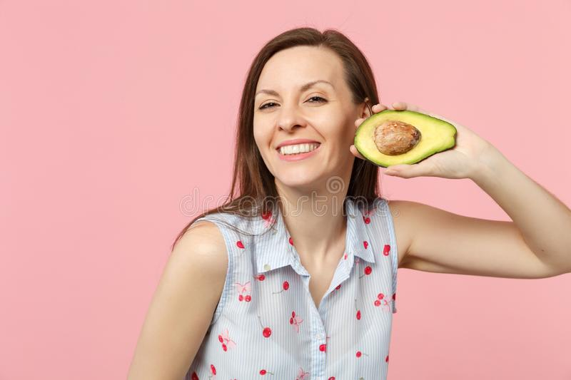 Smiling young woman in summer clothes holding half of fresh ripe green avocado fruit isolated on pink pastel background stock images