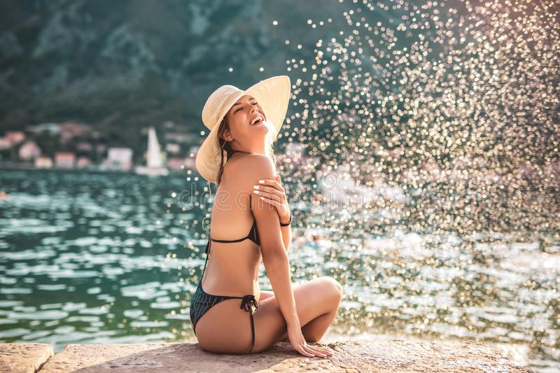 Young woman in sun hat on beach over sea stock photo
