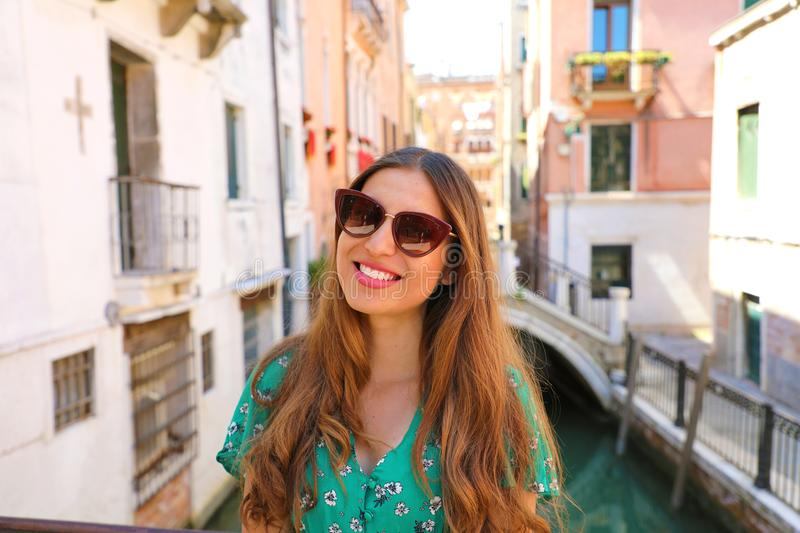 Smiling young woman with sunglasses and green dress in Venice. Happy beautiful girl standing on Venice bridge on canal, Italy royalty free stock photo