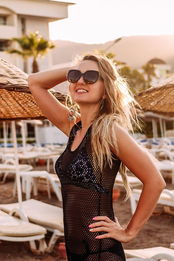 Smiling young woman in sunglasses posing on the beach in contoured sunlight royalty free stock image