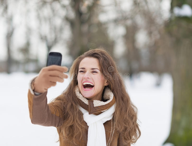 Smiling young woman taking photo using cell phone in winter park royalty free stock photo