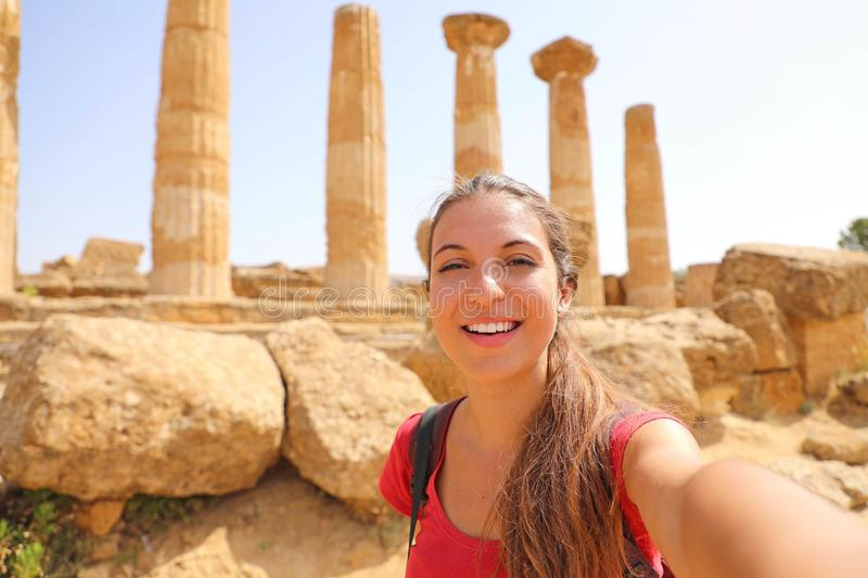 Smiling young woman taking self portrait with greek temple on the background in the Valley of the Temples at Agrigento, Italy.  stock photography