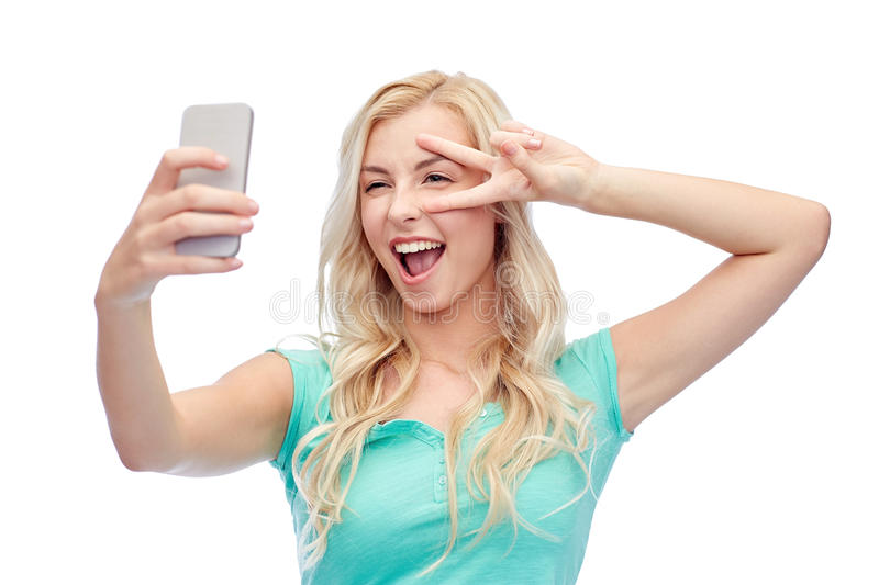 Smiling young woman taking selfie with smartphone. Emotions, expressions and people concept - happy smiling young woman or teenage girl taking selfie with royalty free stock images