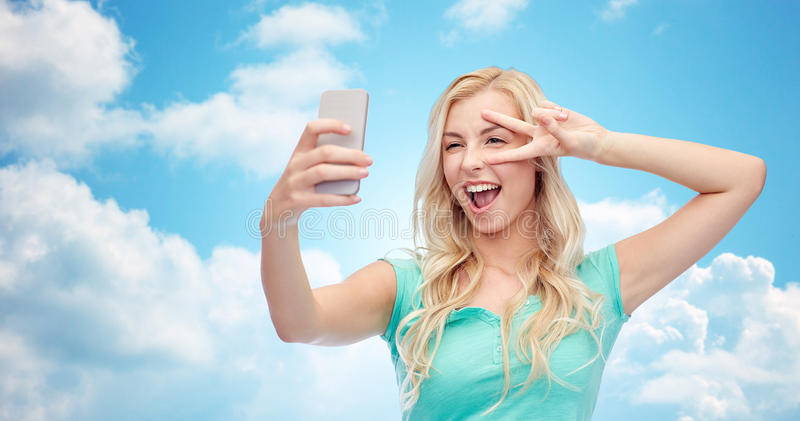 Smiling young woman taking selfie with smartphone. Emotions, expressions and people concept - happy smiling young woman or teenage girl taking selfie with stock images