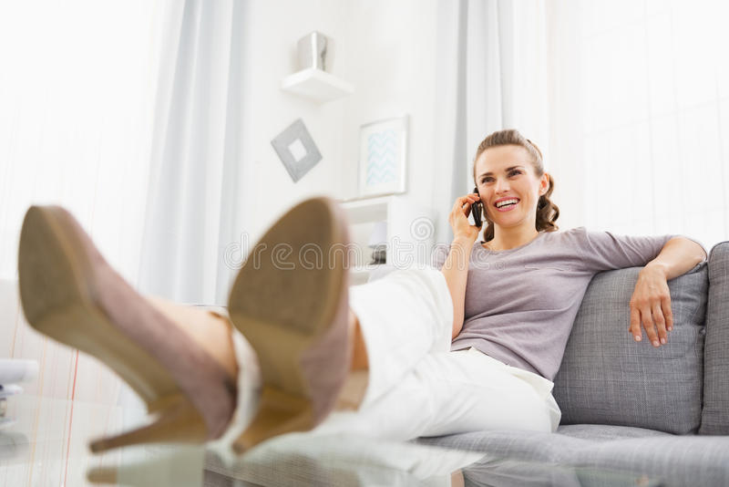 Smiling young woman talking cell phone in living room stock photography