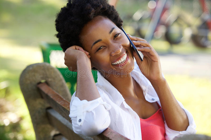 Smiling young woman talking on mobile phone royalty free stock image