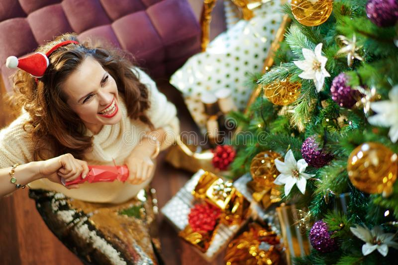 Smiling young woman tearing Victorian Christmas cracker stock images