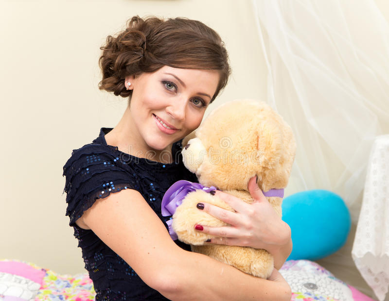 Smiling young woman with teddy bear royalty free stock photography