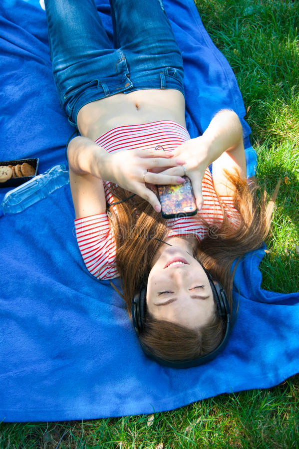 Smiling young woman touching cell phone and lying on the grass royalty free stock image