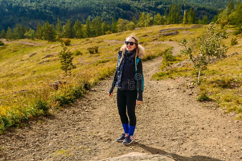 Smiling young woman tourist in the mountains stock photos