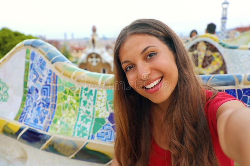 Smiling young woman tourist taking selfie self portrait sitting on the bench decorated with mosaic in famous Park Guell, Barcelona royalty free stock images