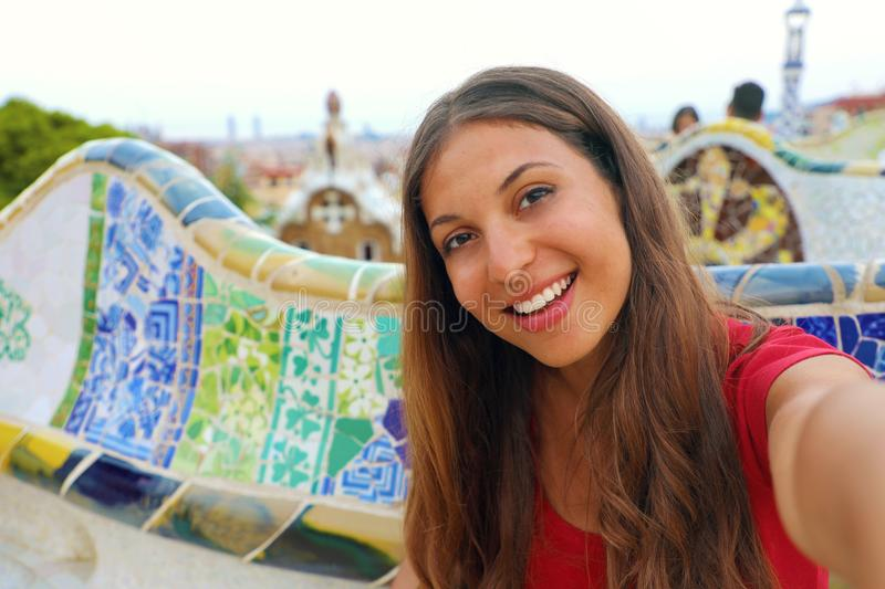Smiling young woman tourist taking selfie self portrait sitting on the bench decorated with mosaic in famous Park Guell, Barcelona royalty free stock photos