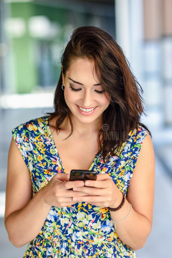 Smiling young woman typing in smart phone outdoors. royalty free stock image