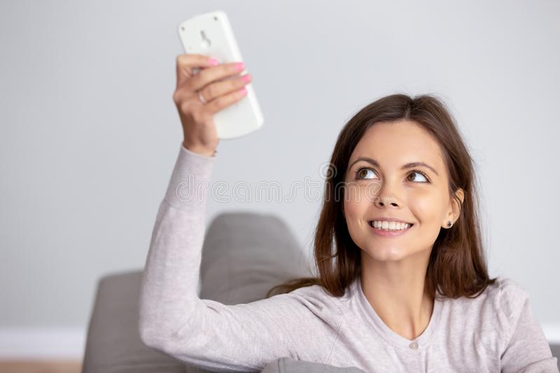 Smiling young woman using air conditioner remote controller close up. Smiling young woman with operating remote controller in hand using air conditioner, resting stock images