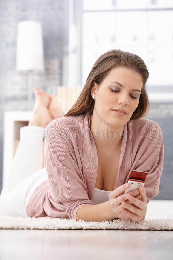 Download Smiling Young Woman Using Cellphone On Floor Stock Photo - Image: 22194044