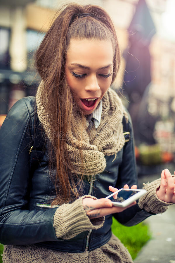 Smiling young woman using mobile on the street royalty free stock photos