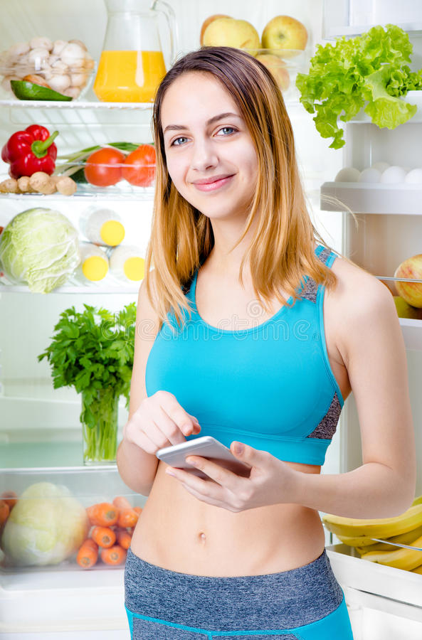 Smiling young woman using a smartphone app and staying near the fridge full of healthy food. Fitness and healthy lifestyle concept stock photos