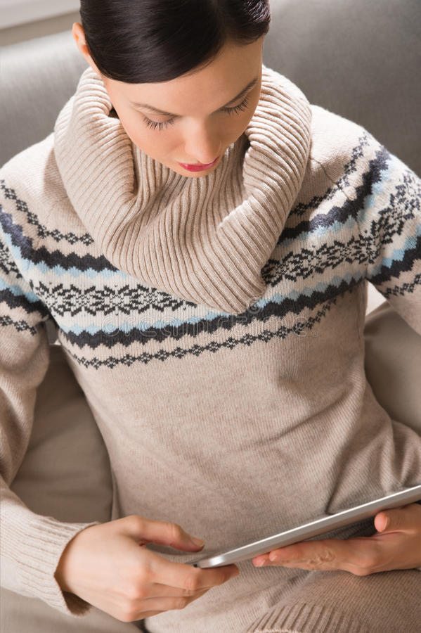 Smiling young woman using tablet computer at home. At night before going to sleep royalty free stock photography