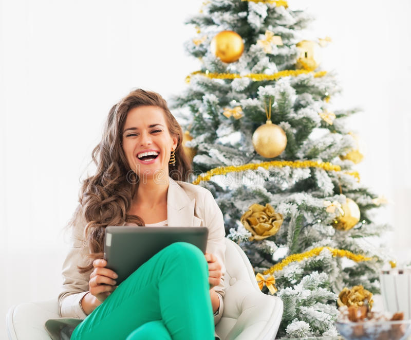 Smiling young woman using tablet pc near christmas tree. In living room stock photo