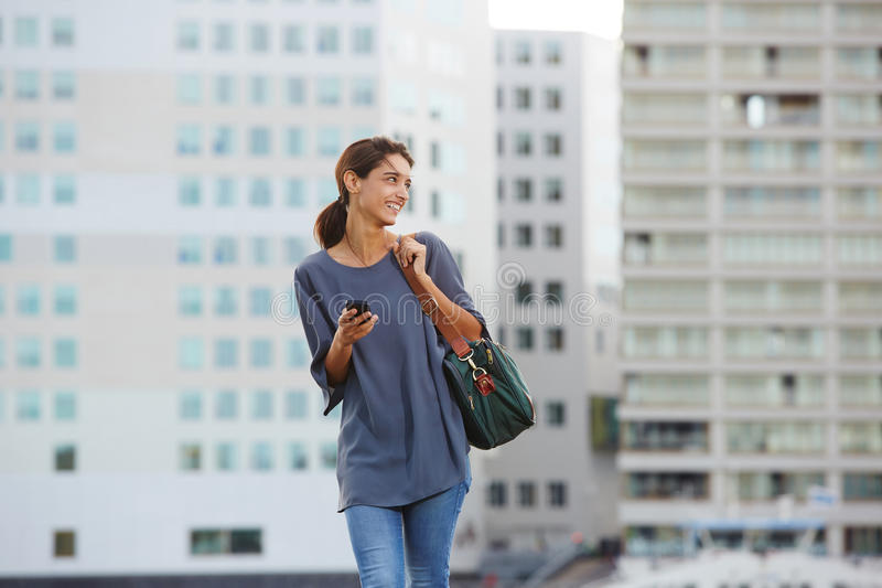 Smiling young woman walking with a bag in city. Portrait of smiling young woman walking with a bag in city stock image