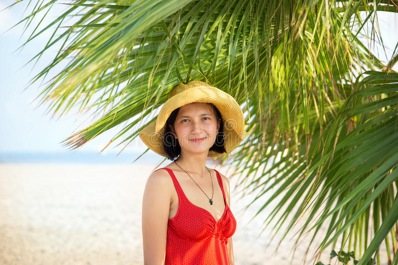 Smiling young woman wearing hat under the palm trees royalty free stock photo