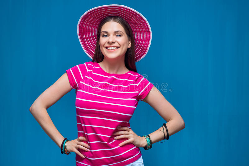 Smiling young woman wearing pink beach hat. Posing against blue background stock photos