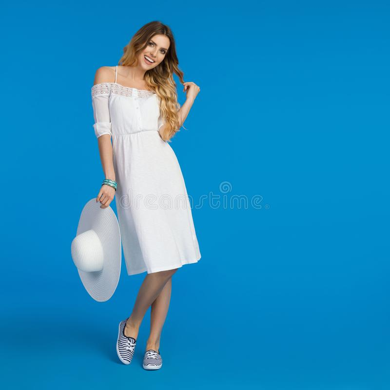 Smiling Young Woman In White Dress Is Holding Sun Hat royalty free stock photo