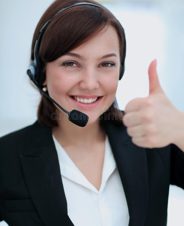 Beautiful woman working at callcenter, using headset showing thu. Smiling young woman working at callcenter, using headset showing thumb up royalty free stock photo